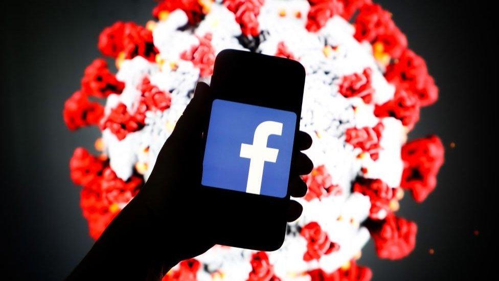 Imagen de un móvil con el logo de Facebook sobre un fondo de un coronavirus
