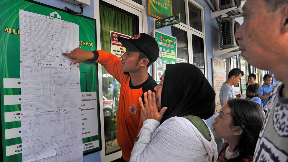 أشخاص يقرأون لوحة بها أسماء