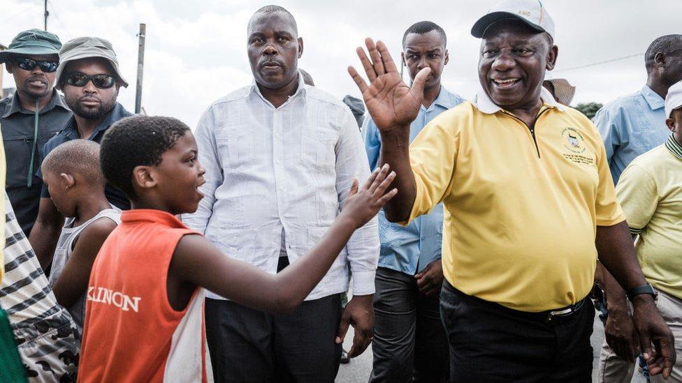 Le président sud-africain et président du parti au pouvoir, l'African National Congress (ANC) Cyril Ramaphosa rend visite aux résidents locaux lors d'une visite de campagne de porte à porte dans le canton de Clermont, le 31 mars 2019