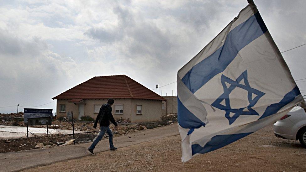رجل يسير في مستوطنة يهودية في الضفة الغربية