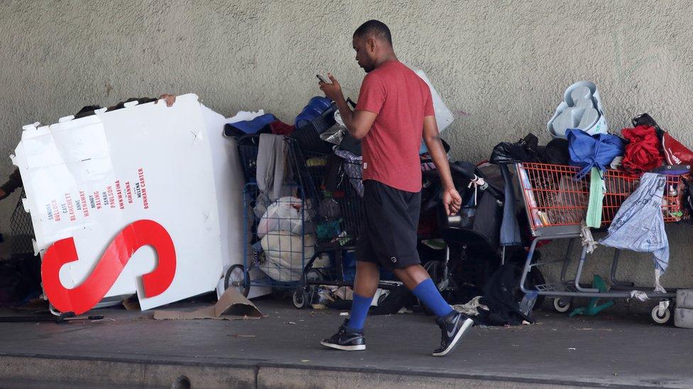 Peatón camina al lado de un habitáculo al aire libre en Los Ángeles