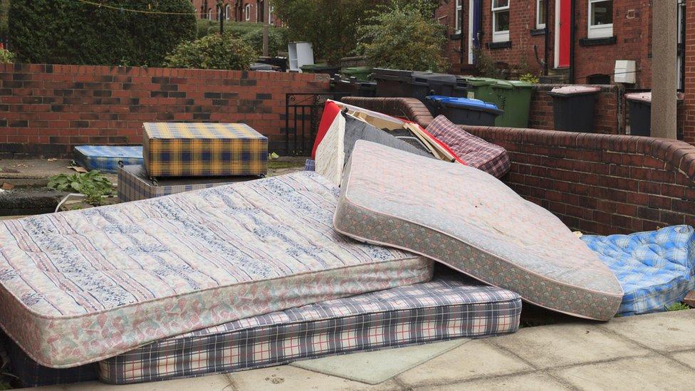 A pile of mattresses outside a house