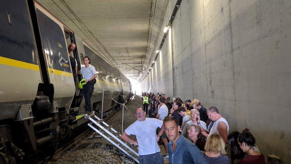 Passengers wait outside the broken down train