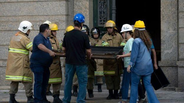 Trabajadores retiran un cuadro quemado del Museo Nacional tras el incendio