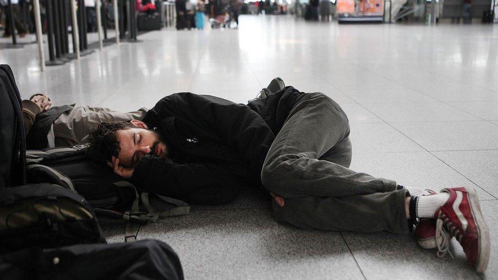chico durmiendo en el suelo del aeropuerto