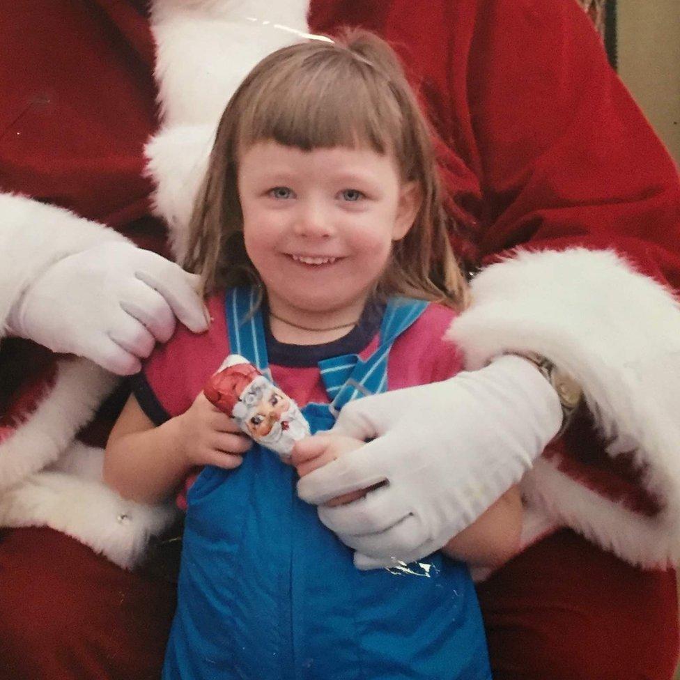 Ashley de niña con un centro comercial con Papá Noel.