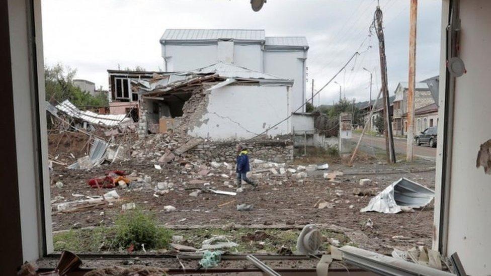 斯捷潘納克特一位居民走過炮戰留下的廢墟(8/10/2020)