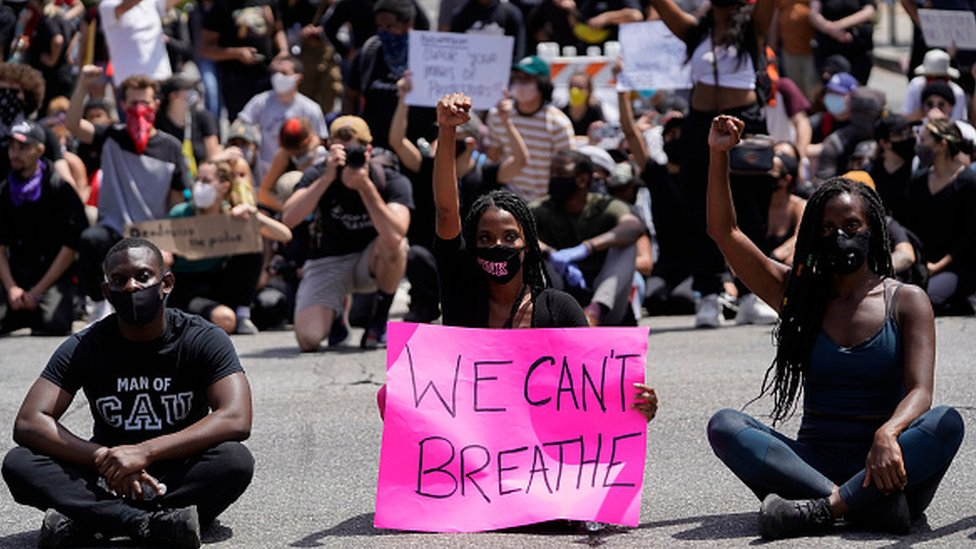 Protesters sit at an intersection during demonstrations following the recent death of George Floyd in Los Angeles, California