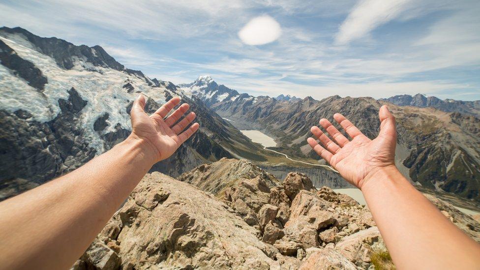 Manos estiradas frente a un paisaje montañoso.