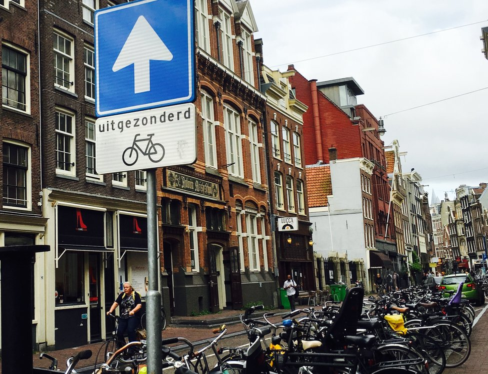 Dutch street sign says one-way except for bicycles