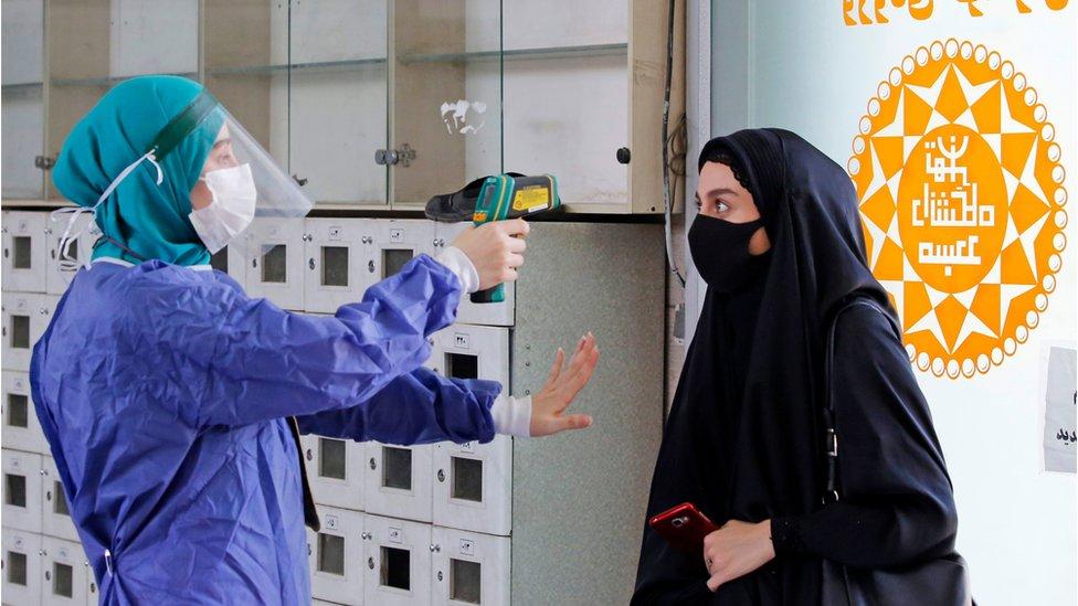 德黑蘭大學校園清真寺入口處一名工作人員給一名進寺女生量體溫(30/7/2020)