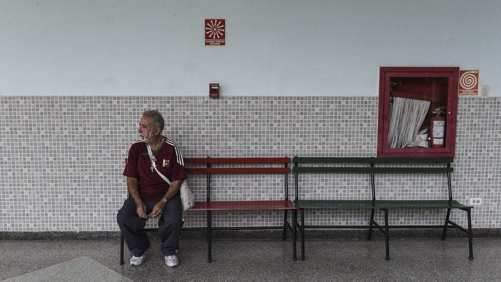 Un señor sentado en un banco en un colegio electoral de Caracas-
