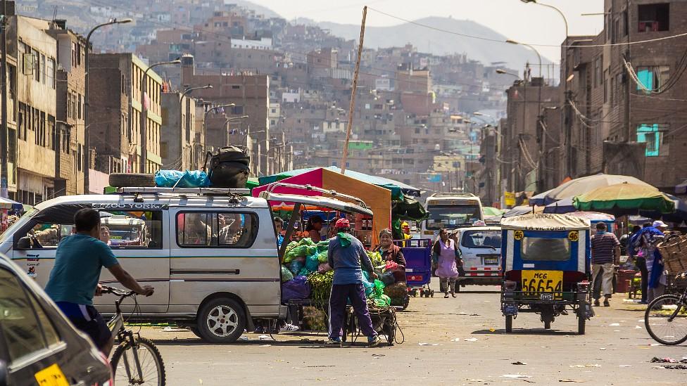 Barrio en la zona periurbana de Lima con trabajadores ambulantes en la calle