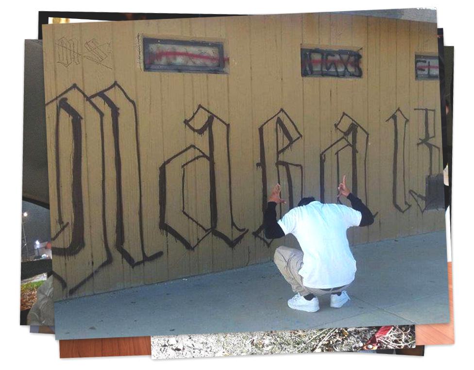 """Un acusado por las muertes del Bosque Nacional Ángeles posa de espaldas y haciendo gestos con las manos alusivos a la MS-13. Al fondo, un grafiti dice """"Mara 13"""""""