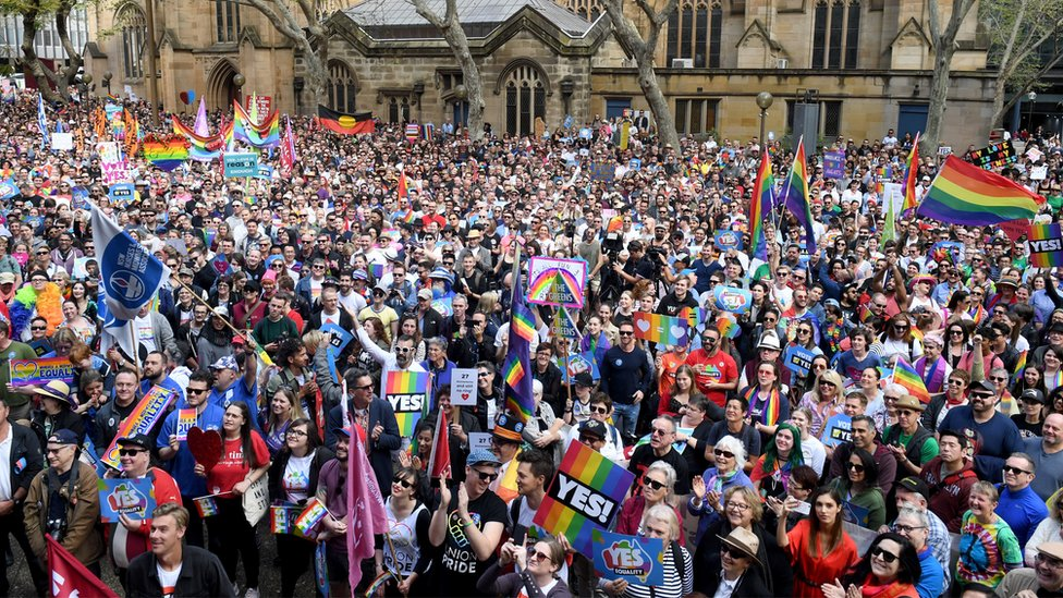 Protestors gathering in central Sydney, thousands are seen with signs and rainbow flags