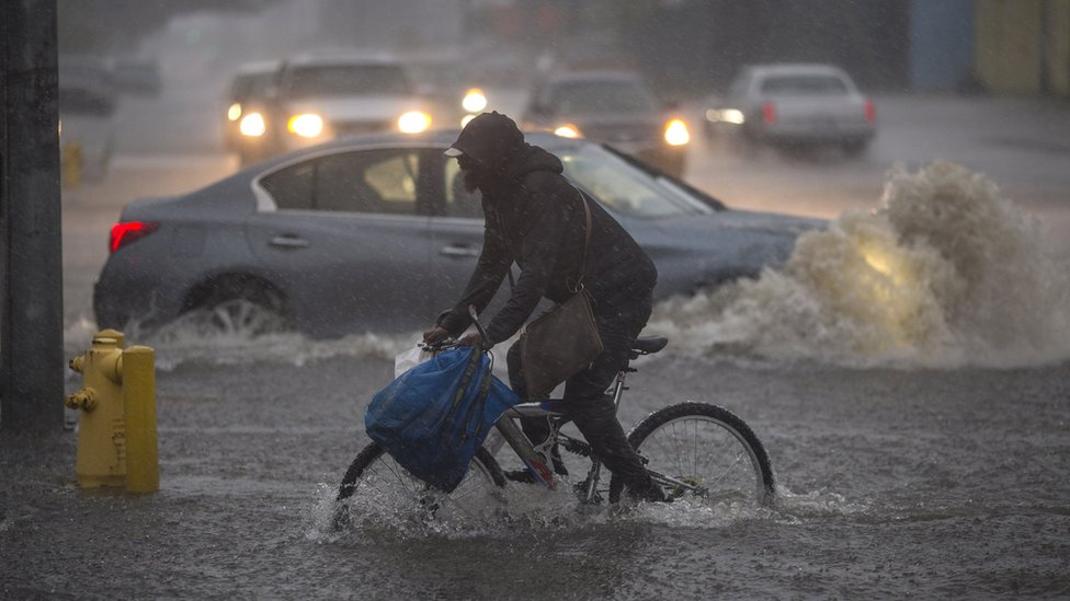 A man tries to cycle through the flooded streets of Sun Valley, southern California