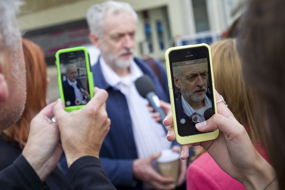 Corbyn speaking while being pictured on mobile phones