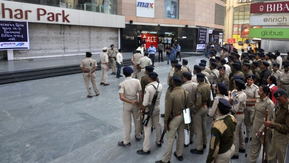 Police stand guard outside a mall in Gujarat