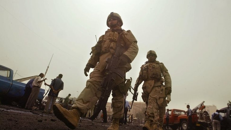 US soldiers patrol along the street of a suicide car bomb attack 9 August 2005, in central Baghdad