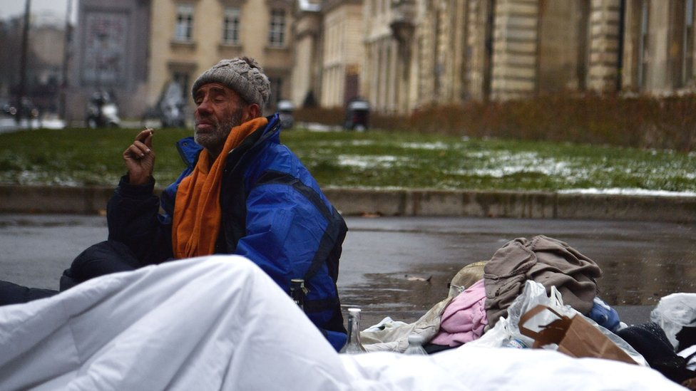 A homeless man sits on the pavement with a duvet in a street of Paris, on 1 March 2018
