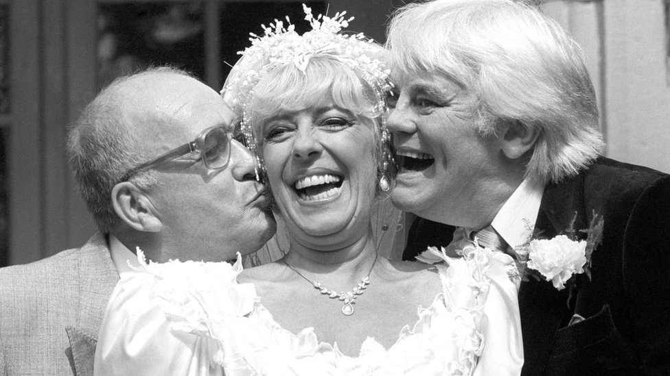 Coronation Street barmaid Bet Lynch (actress Julie Goodyear) getting a kiss from television groom Alec Gilroy (actor Roy Barraclough), and best man Charles Halliday (actor Tony Booth)