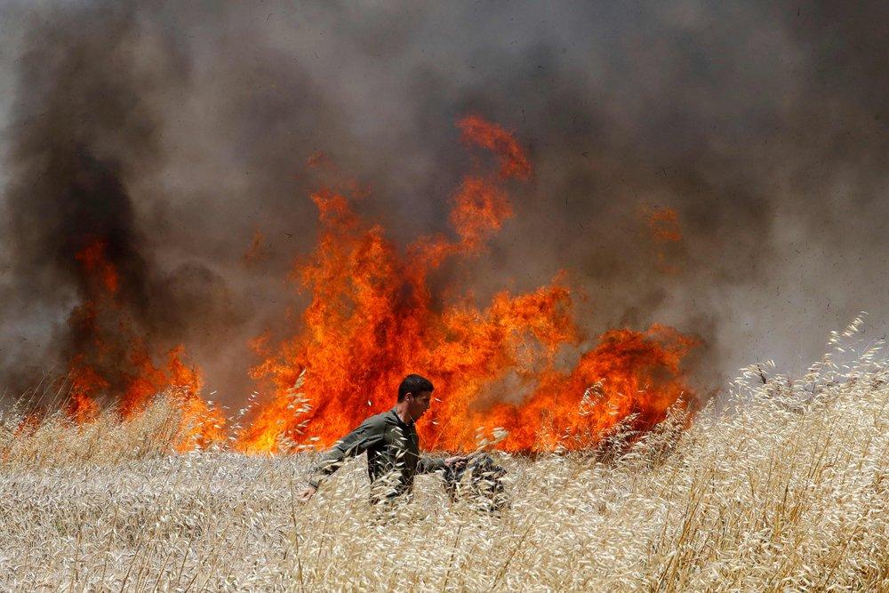 Un soldado israelí intenta apagar un incendio en un cultivo de trigo