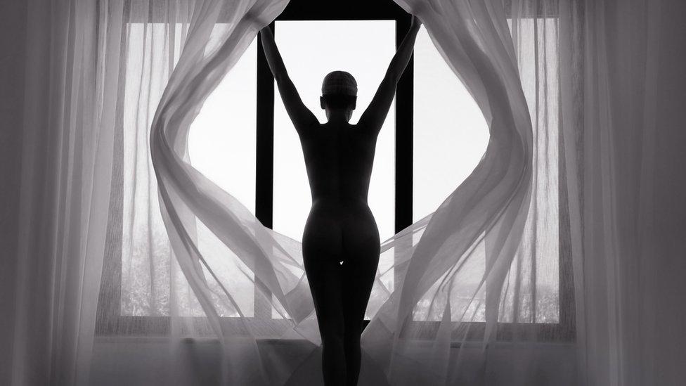 Mujer de espaldas y en silueta contra una ventana