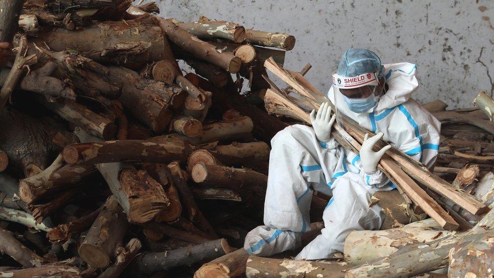 Un familiar sostiene trozos de madera en una pira en India.