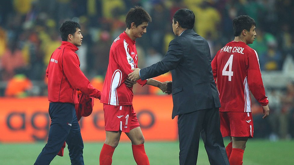 Dejected An Young-Hak of North Korea shakes hands with head coach Kim Jong-Hun after defeat and elimination from the tournament during the 2010 FIFA World Cup