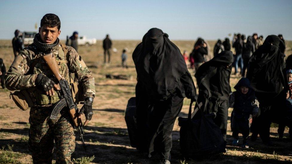 أحد مقاتلي قوات سوريا الديمقراطية يشرف على خروج نساء وأطفال من الباغوز