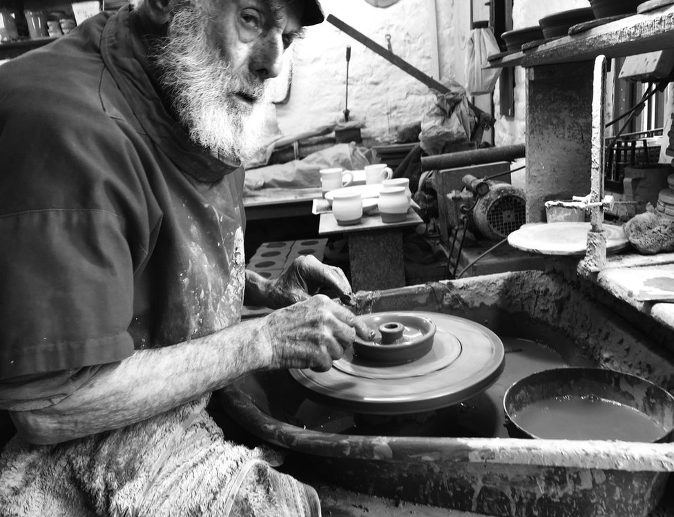 A potter is working with clay on the pottery wheel