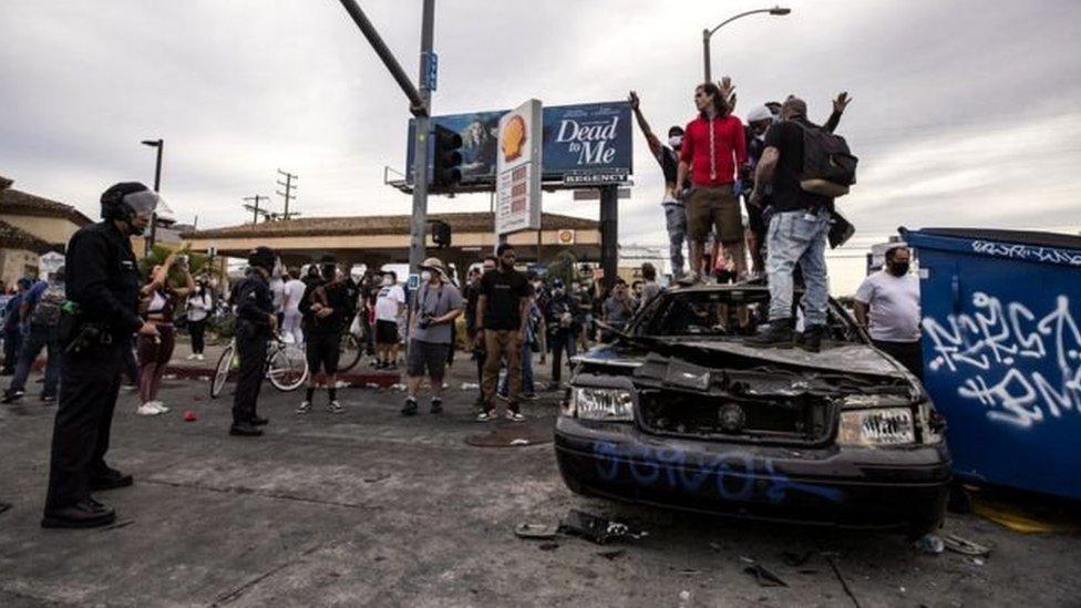 Pengunjuk rasa berdiri di atas mobil polisi yang telah hangus dibakar di Los Angeles, California.