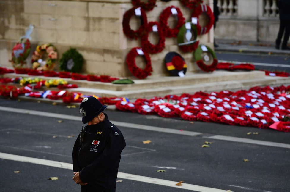 A police officer bows his head during the remembrance service