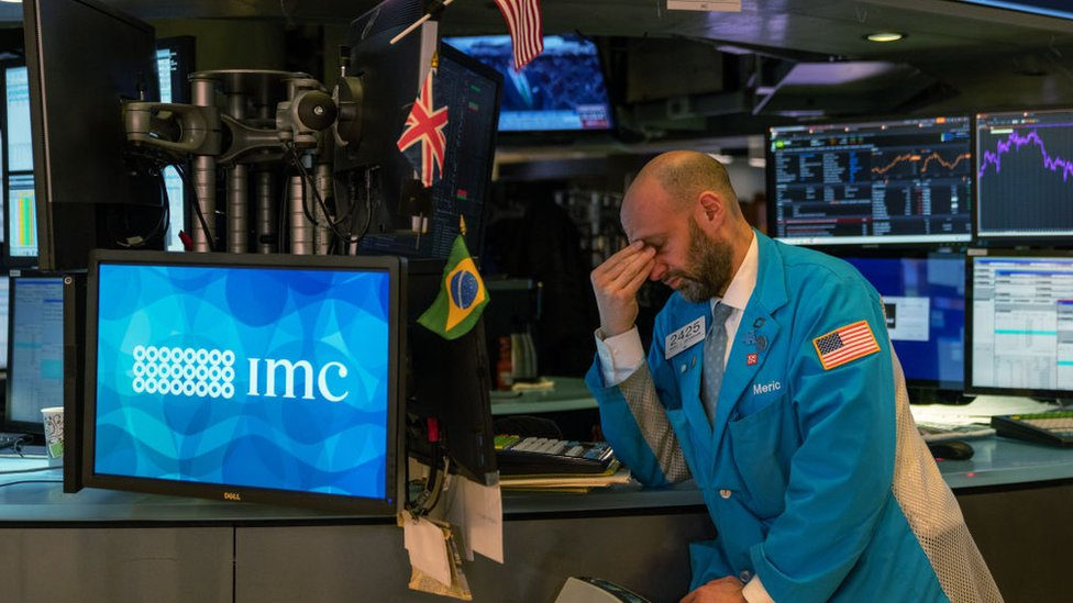 Hombre lamentando las caídas en la Bolsa de Valores de Nueva York.