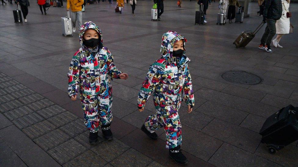deca sa maskama na ulicama pekinga
