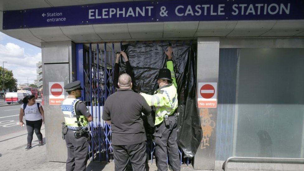 Police officers close the gates at Elephant & Castle station