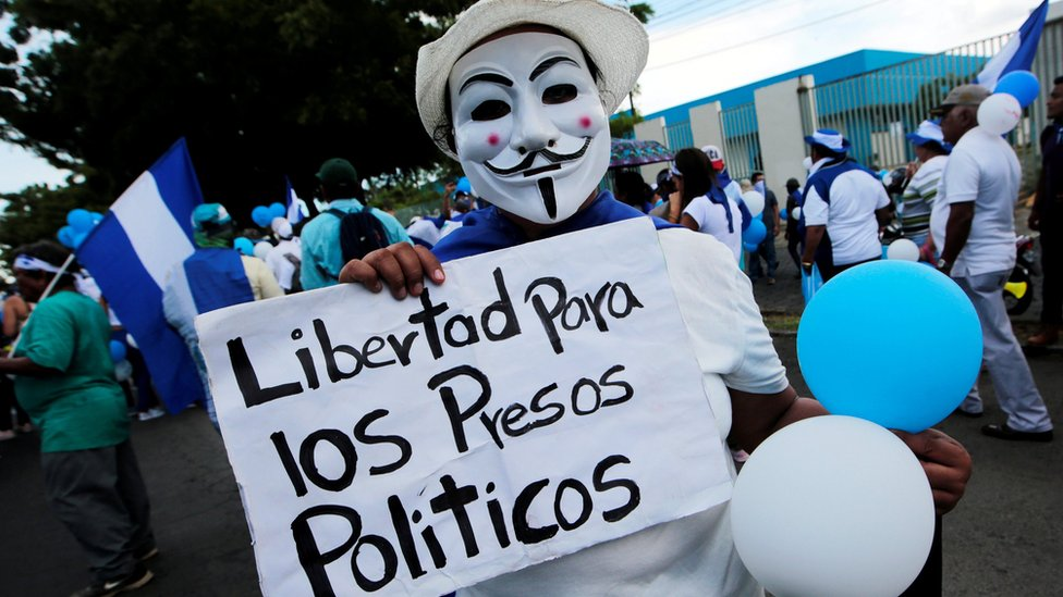 "A masked anti-government protester holds a sign reading ""Freedom for political prisoners"" in Managua, Nicaragua on 9 September 2018."