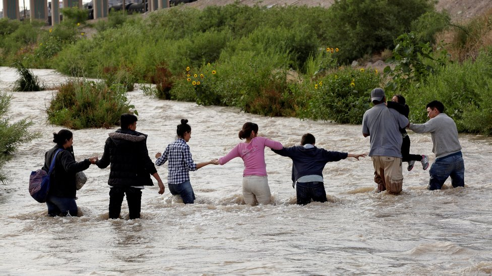 Migrants from Central America form a human chain to cross the Rio Bravo river to enter illegally into the United States to turn themselves in to request for asylum in El Paso, Texas, U.S., as seen from Ciudad Juarez, Mexico June 11, 2019
