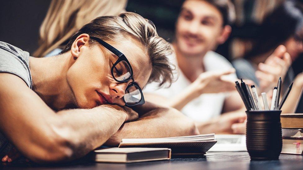 Una estudiante durmiendo sobre sus libros.