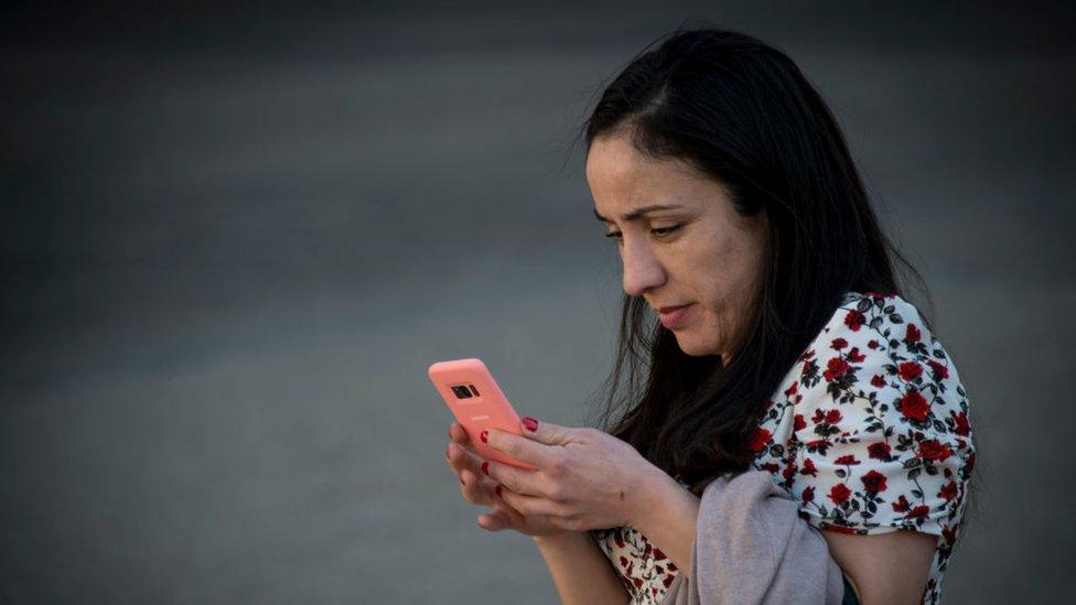 Mujer usando un celular en Santiago de Chile