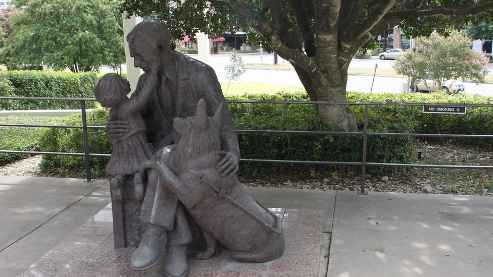A statue of a man and his guide dog interacting with a little girl outside the Texas School for the Blind and Visually Impaired