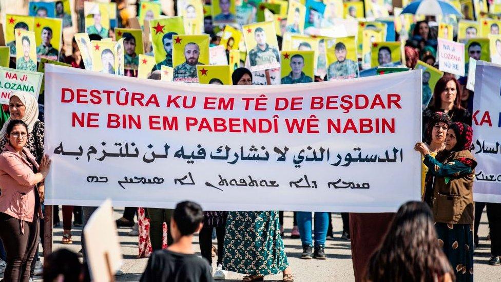 Salı günü Suriye'nin Kamışlı kentindeki BM binası önünde gösteri düzenleyenler, Suriyeli Kürt siyasi oluşumlarının Komite'de temsil edilmemesini protesto etti.