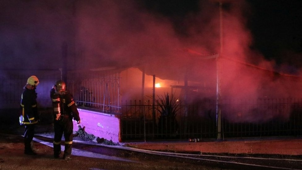 Firefighters stand next to the burning premises of a refugee centre on the island of Lesbos, Greece