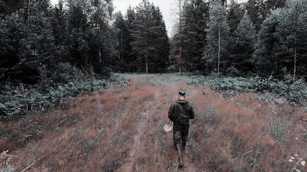 Mužčina idet po lesu