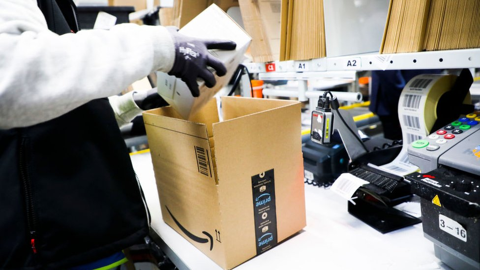 An Amazon worker wearing gloves, packing items into a box