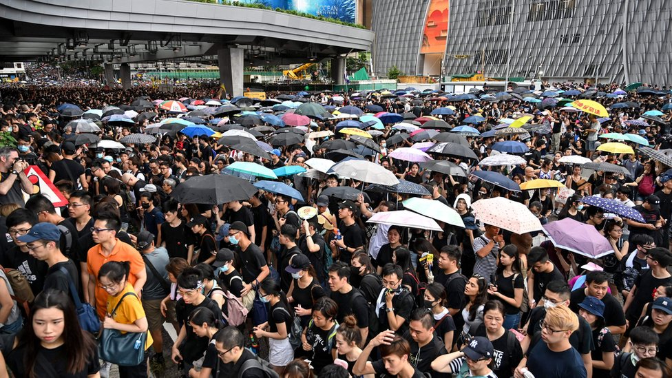 Protesters carry umbrellas during a march to the West Kowloon rail terminus against the proposed extradition bill and before a clash with police in the Mong Kok district in Kowloon in Hong Kong on July 7, 2019