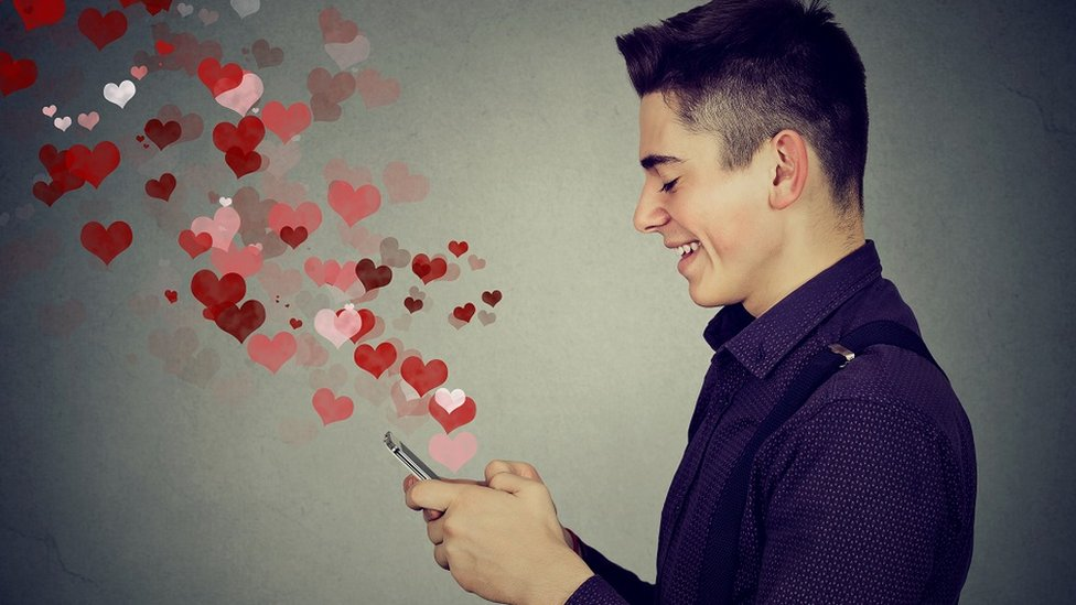 A young man using a smartphone to send love messages