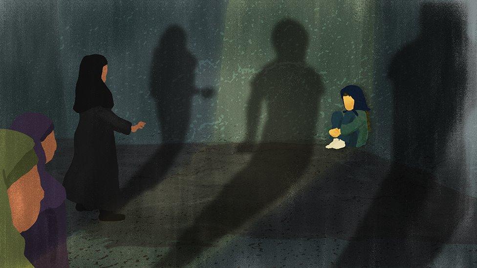 Tres mujeres se acercan a una niña asustada, que está sentada en la esquina de una habitación oscura.