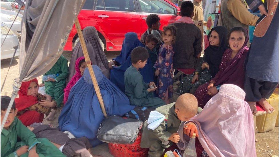نساء وأطفال غلبهم التعب وهم ينتظرون في الطقس الحار