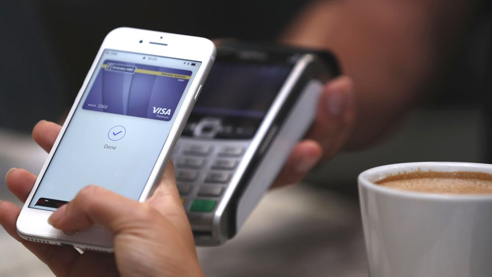 An iPhone being used to pay for a coffee